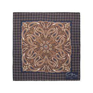Pañuelo estampado con arabescos cafés, fondo azul oscuro y cenefa de figuras geométricas en seda de origen Español.